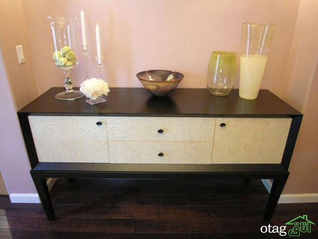 Living room console table with glass vase, candlesticks, decor and hardwood floor.